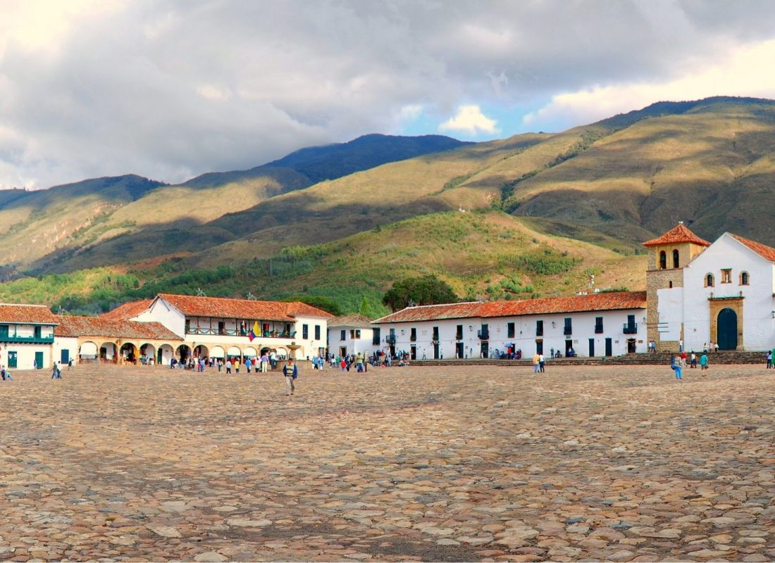 The main square of Villa de Leyva, one of the biggest colonial square in South America, with Nuestra Señora del Rosario church on the right hand side and the beautiful mountains in the background.
